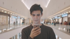Young men using smartphone at shopping mall. Portrait Stock Footage