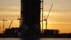 Tower construction site silhouetted against sunset sky, time lapse shot Stock Footage