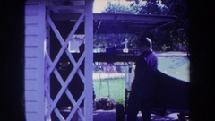 1969: residential area man standing in veranda VOLMER YUCAIPA CALIFORNIA Stock Footage
