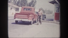 1957: a man at the side of a busy road who walks from a truck towards a car and Stock Footage