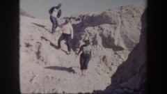 1957: a group of people carefully going down a sandy slope ARIZONA Stock Footage