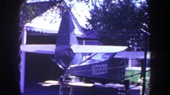 1969: small plane marked n2228 is parked outside of garage by worktable, tree Stock Footage