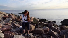 Young adult woman sit alone at stony beach, play with toy dog, slow motion Stock Footage