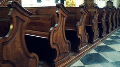 Old wooden benches in catholic church Stock Footage