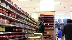 Grocery clerk stocking food for sale inside T&T Chinese supermarket Arkistovideo