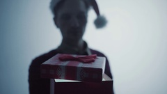 Young man in red Santa Claus hat openinng gift box surprised and happy with what Stock Footage