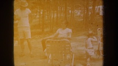 1968: countryside family picnic party, father sitting with his toddler. MICHIGAN Stock Footage