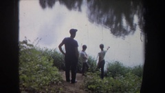 1968: three boys standing together near a lake and coming back catching a big Stock Footage