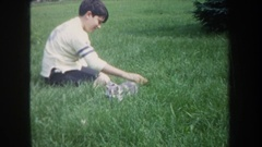 1968: child pets and plays with group of kittens in uncut grassy area. MICHIGAN Stock Footage