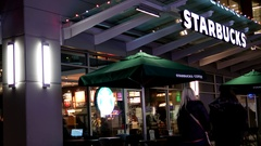 People enjoying coffee inside Starbucks coffee at night with 4k resolution. Stock Footage