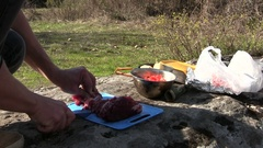 Cooking  food outdoors. Man cuts meat Stock Footage