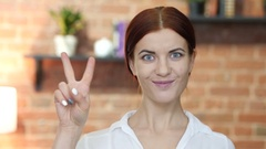 Woman Showing Victory Sign, Indoor Stock Footage