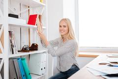 Young business woman taking book from a shelf in office Stock Photos