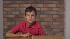 Child sitting at the desk holding flipchart with lettering trend on the Stock Footage