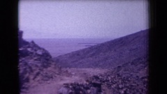 1958: desert environment with a dirt path near a rocky outcrop and people Stock Footage