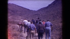 1958: a small group of men and women follow a trail up a shallow hill, while Stock Footage