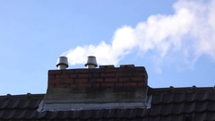 White smoke coming out of roof chimneys on a cold and frosty morning Stock Footage