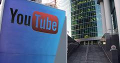 Street signage board with Youtube logo. Modern office center skyscraper and Piirros