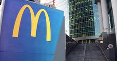Street signage board with McDonald's logo. Modern office center skyscraper and Stock Illustration