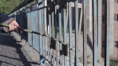 Girl walks and knocks with stick on the fence Stock Footage