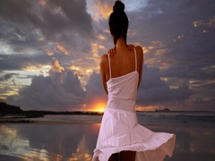A Latina girl dances in a sundress at sunset on the beach Stock Footage