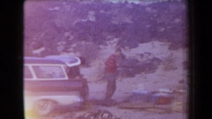 1958: a group of young men take stock of their belongings in a natural setting Stock Footage