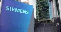 Street signage board with Siemens logo. Modern office center skyscraper and Stock Illustration