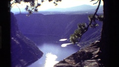 1980: a canyon cut through by a river with the sun reflecting off of it behind Stock Footage