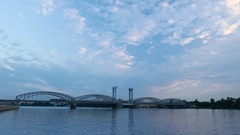 Heavy cargo train ride at steel railway bridge, wide angle panorama, evening sky Stock Footage