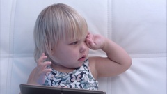 Baby girl with tablet rubbing her eyes after crying Stock Footage