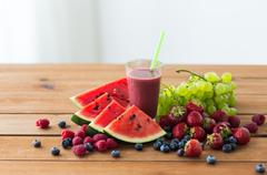 Fruit and berry juice or smoothie on wooden  table Stock Photos