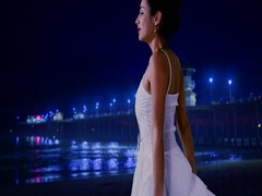 A Hispanic woman looks off on the waves, lit by a blue pier Stock Footage