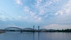 Steel arched railway bridge stretched across river, evening to night timelapse Stock Footage
