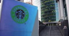 Street signage board with Starbucks logo. Modern office center skyscraper and Stock Illustration
