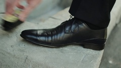 Businessman cleans shoes black shoe polish at the summer street Stock Footage