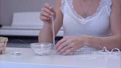Young woman assembling her handmade jewelry Stock Footage