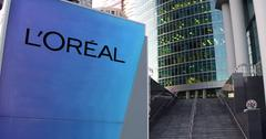 Street signage board with L'Oreal logo. Modern office center skyscraper and Stock Illustration