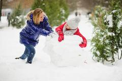 Mother with daughter of younger school age build a snowman in the park. Stock Photos