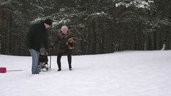 Parents running with their child on a sled in the winter park 96fps Stock Footage