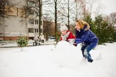 Mother with daughter of younger school age build a snowman in the yard. Stock Photos