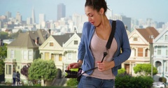 A Latina woman takes pictures of the Painted Ladies in San Francisco Stock Footage