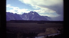 1980: mountains divide sky and clouds from flatlands bordered by stream and Stock Footage