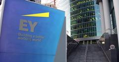 Street signage board with Ernst and Young logo. Modern office center skyscraper Stock Illustration
