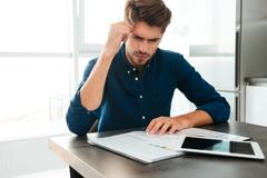 Concentrated young man analyzing his finances at home Stock Photos