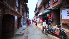 Street of Bhaktapur with stores, bikes, busy local people. Nepal Stock Footage