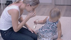 Happy young mother and her little daughter exploring the jewelry box sitting on Stock Footage