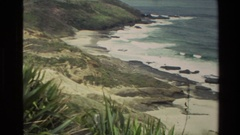 1981: camera panning over a beach that has a somewhat rocky coastline and waves Stock Footage