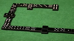 Configuration of played black domino tiles on green table Stock Footage