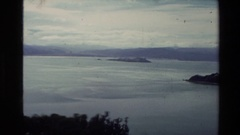 1981: panoramic view of an ocean with a rock area jutting into the sea with Stock Footage