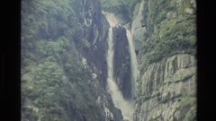 1982: tall waterfall flowing down a narrow drop between granite rock NEW ZEALAND Stock Footage